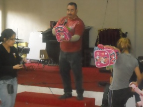 Pastor Jose helping hand out backpacks